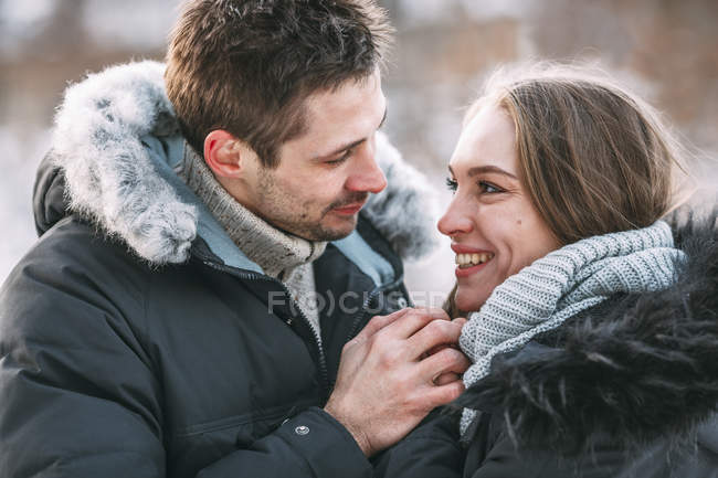 Smiling young couple posing face to face and holding hands — Stock Photo