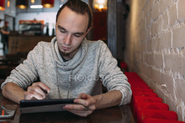 Young man using digital tablet at cafe — Stock Photo