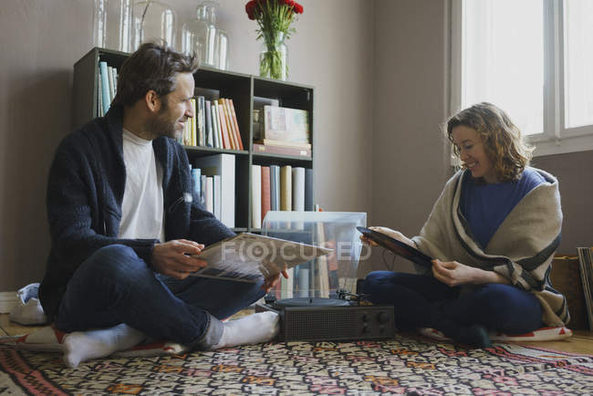 Happy couple sitting with records by turntable on carpet at home — Stock Photo