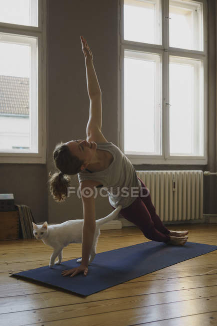 Woman practicing side plank pose on exercise mat by cat at home — Stock Photo