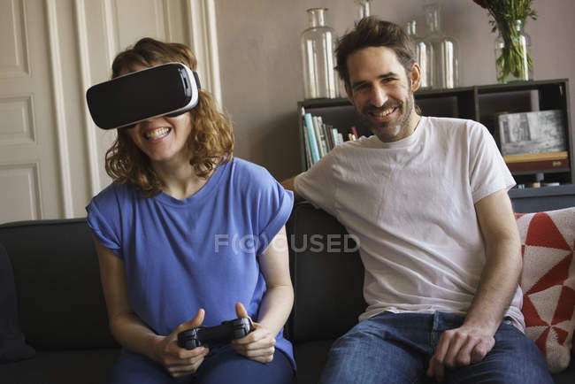 Portrait of smiling man sitting by woman playing on virtual reality headset at home — Stock Photo