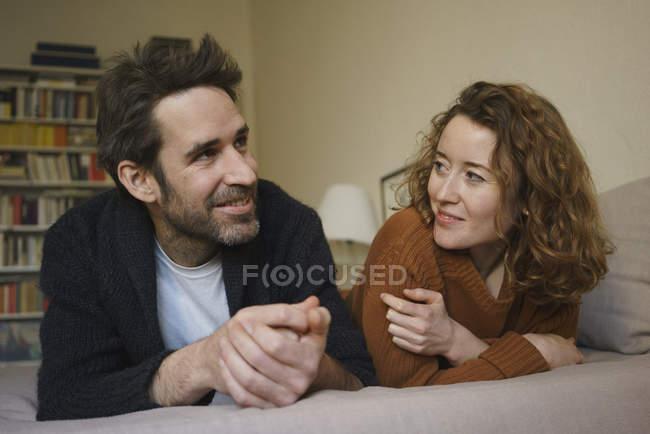 Casal feliz, deitado na cama em casa — Fotografia de Stock