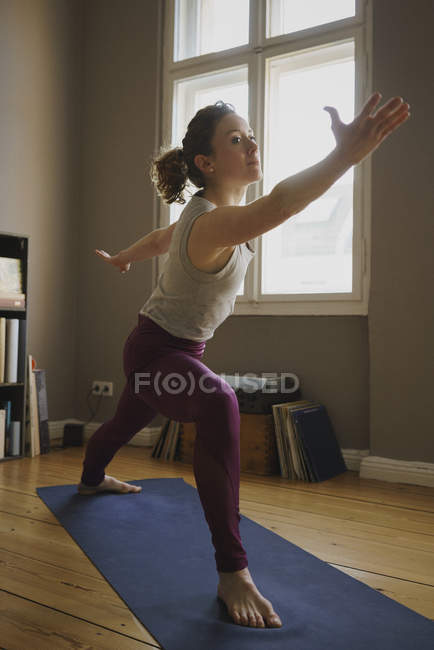 Woman practicing warrior 2 position on exercise mat at home — Stock Photo