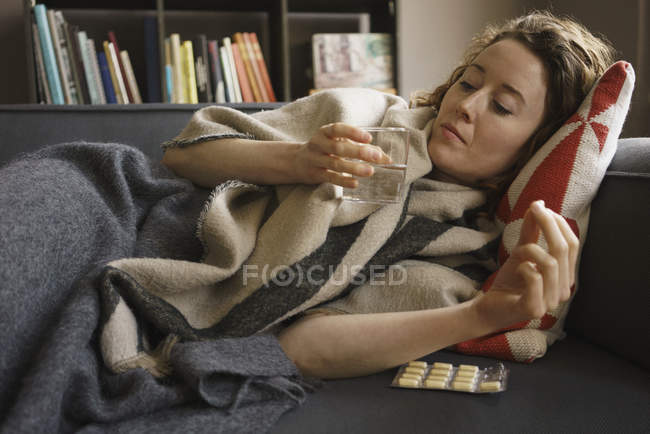Woman taking medicine while lying on sofa in living room at home — Stock Photo