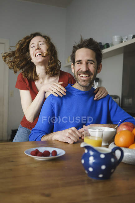 Portrait of man with laughing woman at table with breakfast in room — Stock Photo