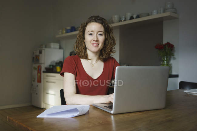 Confident woman sitting with laptop and tax forms at table in kitchen — Stock Photo