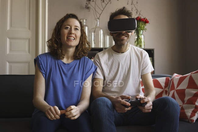 Smiling woman sitting by man playing on virtual reality headset in living room at home — Stock Photo