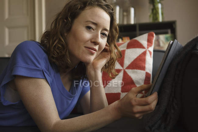 Portrait of confident woman using digital tablet on sofa and looking at camera — Stock Photo