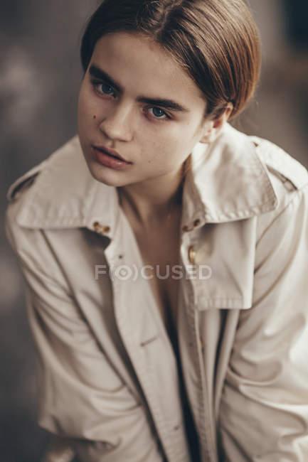 Portrait d'une adolescente portant un trench coat et regardant la caméra — Photo de stock