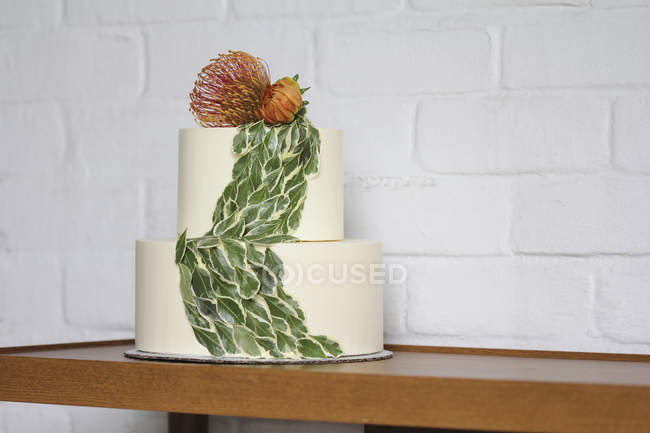 Fresh cake with flower decoration against white brick wall — Stock Photo