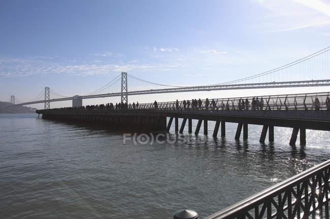 Vista lateral do cais com Oakland Bay Bridge sobre a baía, no fundo, São Francisco, EUA — Fotografia de Stock