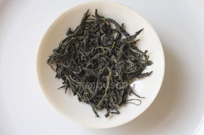 Vista directamente encima de té fresco hojas de placa sobre fondo blanco - foto de stock