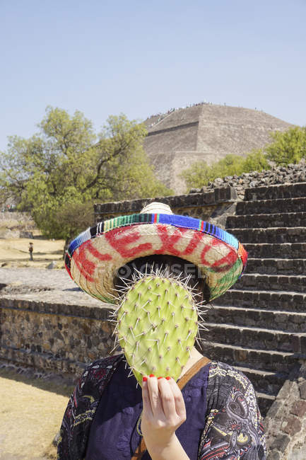 Woman wearing sombrero and hiding face with prickly pear cactus over pyramids — Stock Photo