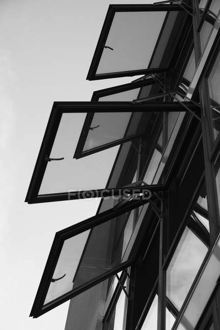 Low angle view of open windows of building against sky — Stock Photo