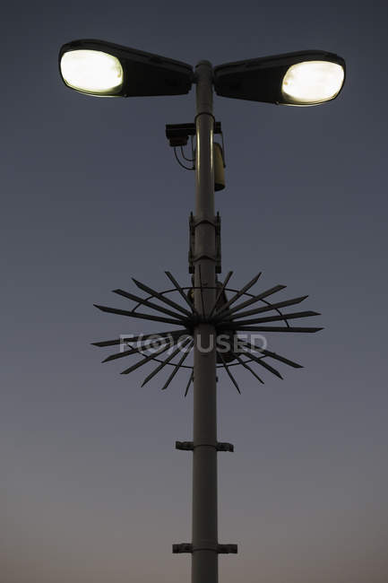 Low angle view of illuminated street light and surveillance cameras against sky — Stock Photo