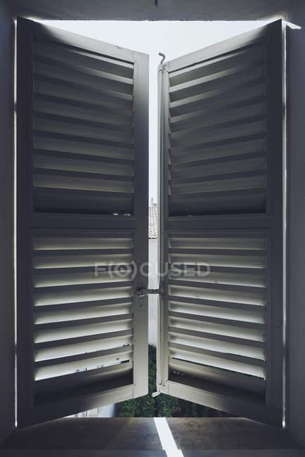Sunlight behind white wood shutters — Stock Photo