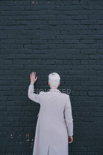 Mujer de pie y tocar el muro negro - foto de stock