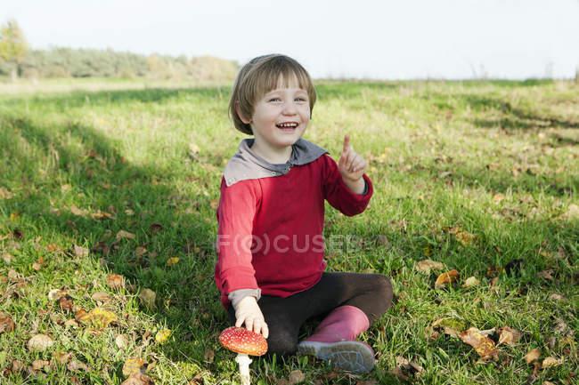 Портрет счастливая девушка сидит рядом с грибом — стоковое фото