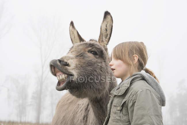 Jeune fille debout à côté de l'âne — Photo de stock