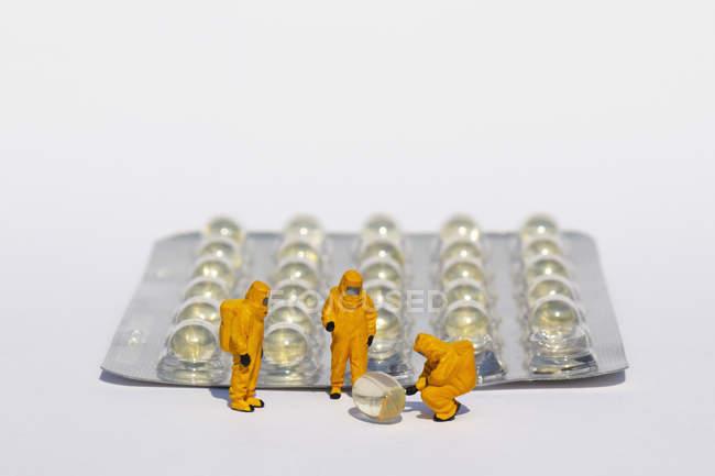 Piccoli scienziati in tute pulite esaminando gel capsule dal blister pack — Foto stock