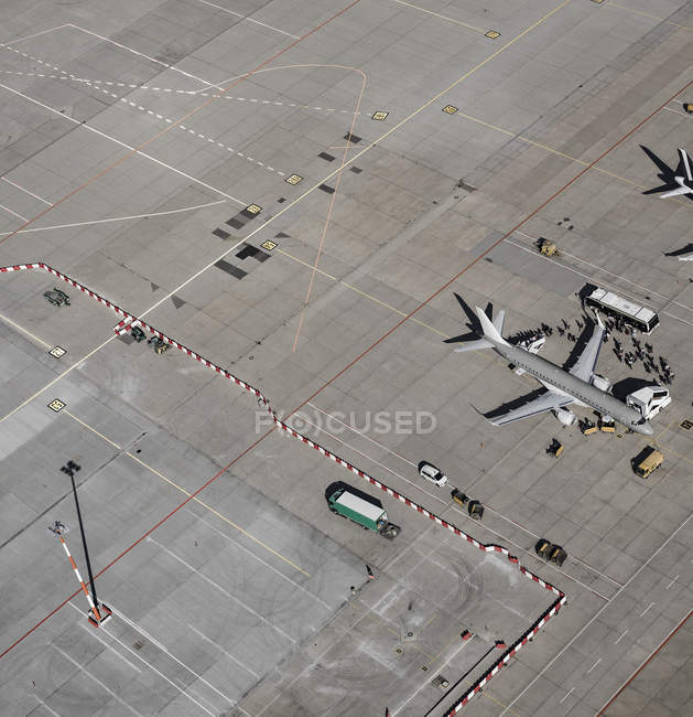 Aerial view of passengers boarding commercial airplane on tarmac at airport — Stock Photo