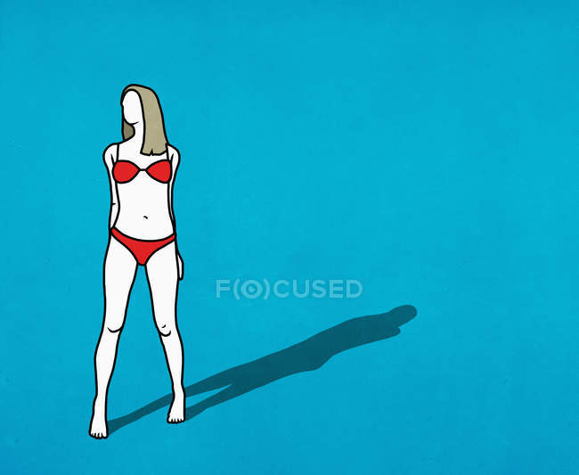 Confident woman in red bikini on blue background — Stock Photo