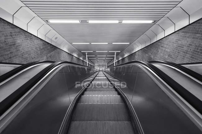 Black and white of descending escalator — Stock Photo