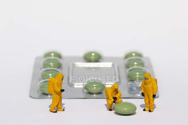 Petits scientifiques en costumes propres examinant la pilule verte de la plaquette thermoformée — Photo de stock