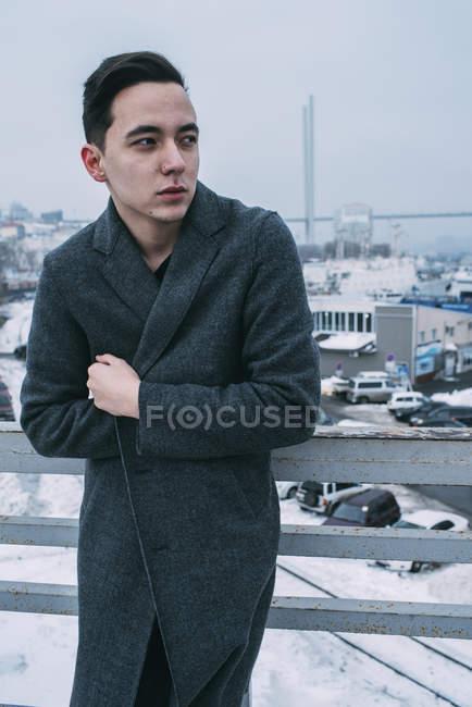 Jeune homme en manteau long sur un pont d'hiver urbain — Photo de stock