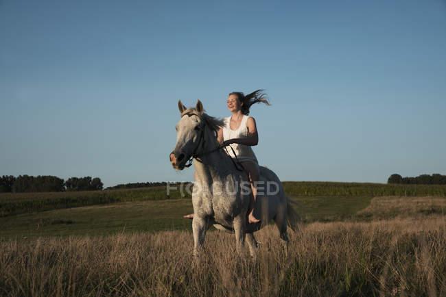 Девушка верхом на лошади в солнечной, сельской местности — стоковое фото