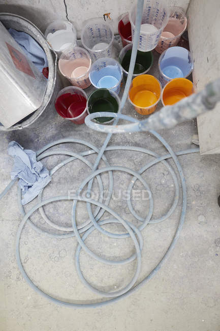Vibrant, multicolor paint in buckets and hose — Stock Photo