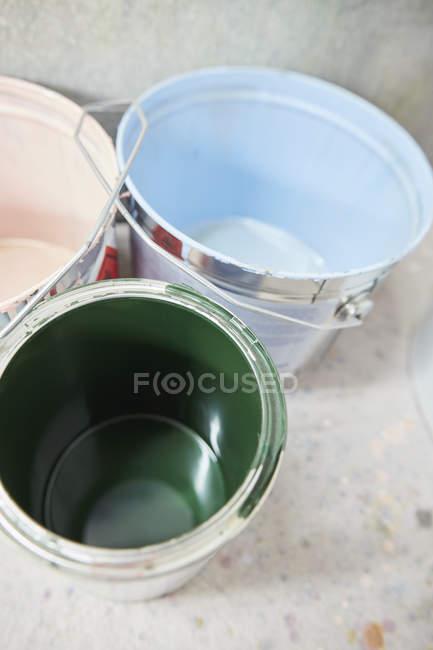 Rosa, azul y verde pintura en latas de pintura - foto de stock