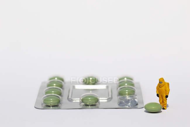 Pequeno cientista em terno limpo examinando pílula verde da embalagem blister — Fotografia de Stock