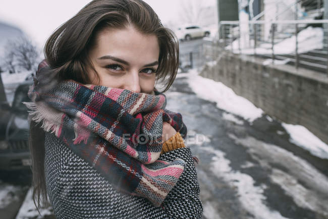 Portrait confident young woman in plaid scarf on snowy winter street — Stock Photo