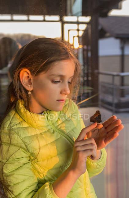 Papillon je regarde fille curieuse sur doigt — Photo de stock
