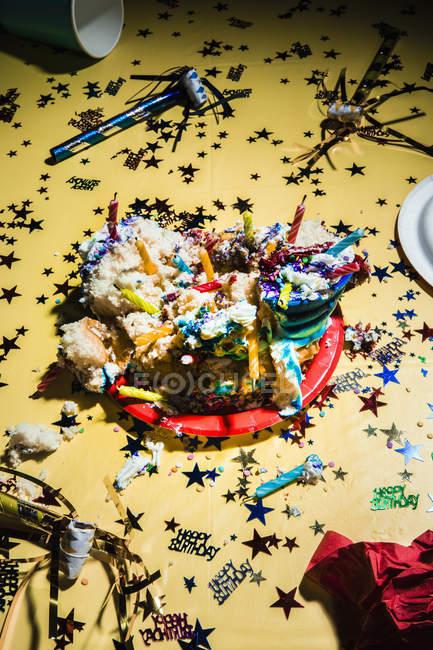 Bolo de aniversário desarrumado e confetes em fundo amarelo — Fotografia de Stock