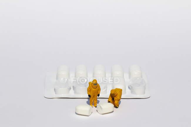 Pequeños científicos en trajes limpios examinar comprimido blanco de blister pack - foto de stock
