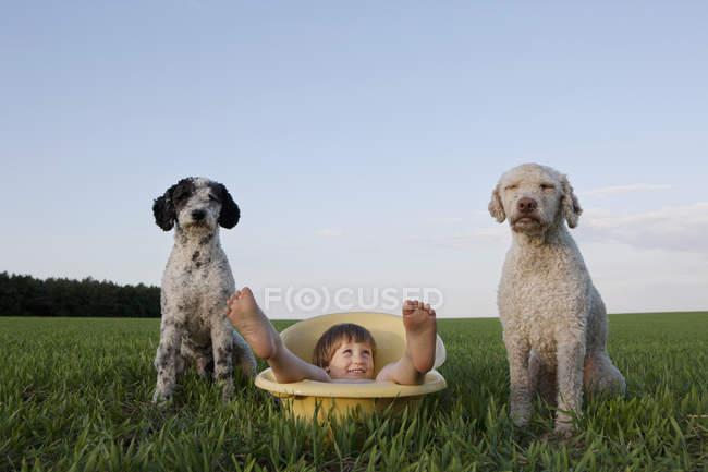 Menina lúdica de retrato na banheira ao lado de cães no campo rural — Fotografia de Stock
