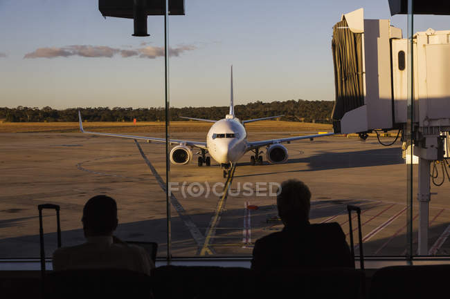 Avião se aproximando da ponte de embarque de passageiros no aeroporto — Fotografia de Stock