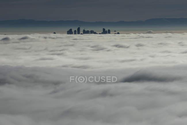 Силуетними хмарочос будинках вище хмар, Ванкувер, Британська Колумбія, Канада — стокове фото
