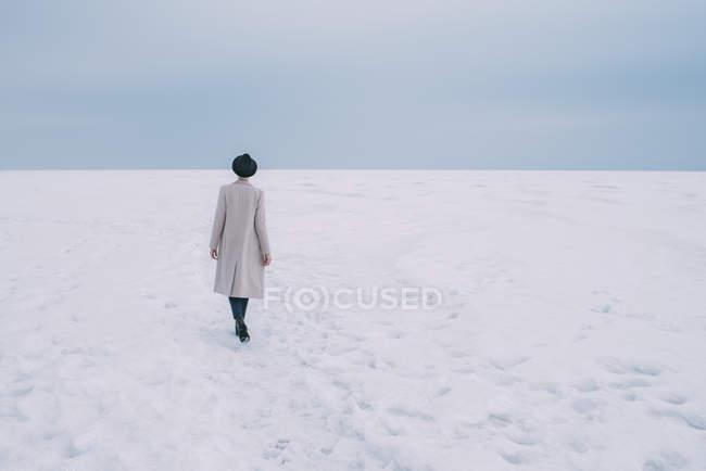 Frau in Mantel und Hut geht durch verschneite Landschaft — Stockfoto