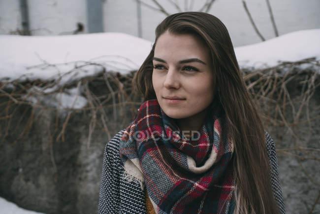 Nachdenkliche junge Frau in kariertem Schal schaut weg — Stockfoto