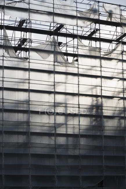 Protective sheeting over highrise building under construction — Stock Photo