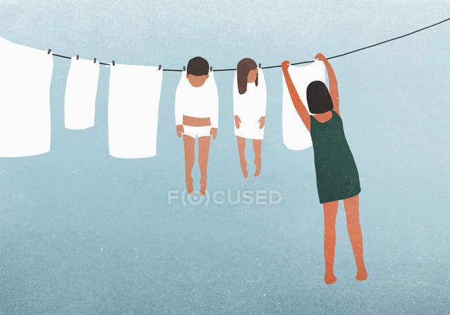 Mulher pendurado crianças no varal para secar — Fotografia de Stock