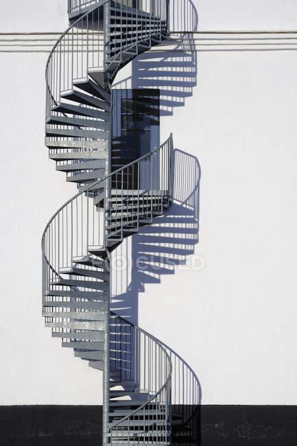 Wendeltreppe und Tür entlang sonniger Wand — Stockfoto