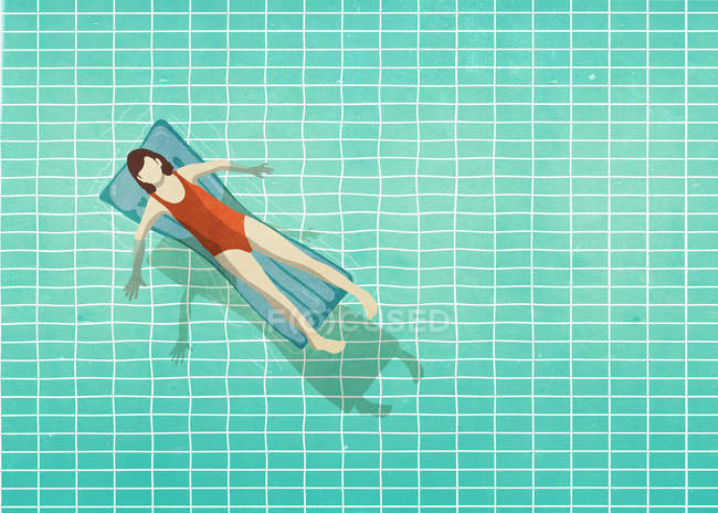 Woman in bathing suit laying on inflatable raft in swimming pool — Stock Photo