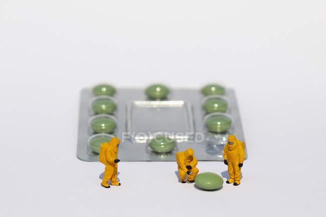 Pequenos cientistas em ternos limpos examinando pílula verde de blister — Fotografia de Stock