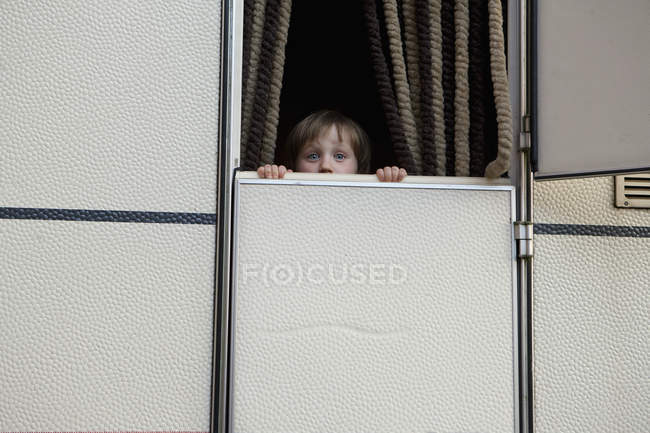 Portrait cute, curious girl peeking from behind trailer door — Stock Photo
