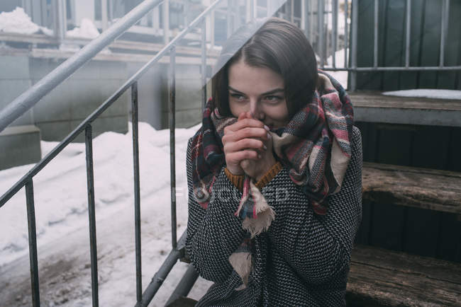 Young woman warming hands on cold, winter stoop — Stock Photo