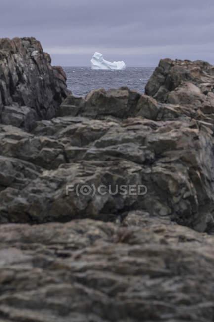 Перегляд айсберг у морі через гірські породи на березі, Фого острова Ньюфаундленд, Канада — стокове фото